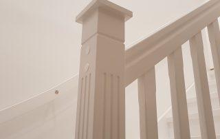 Vit målad l-trappa i massiv furu med rakt blocksteg.