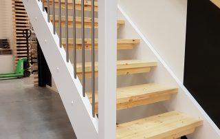 Rak trappa i massiv furu, trappsteg klarlackade, vanger och stolpar vitmålade samt rostfria räckeståndare.