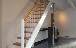 Rak trappa med vita vanger och sättsteg. Trappsteg och handledare i lackad ek.