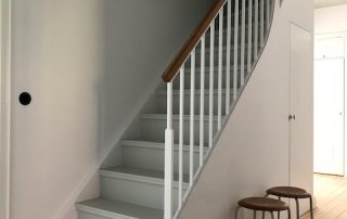 Vitmålad trappa med stålsmide.