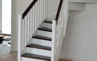 Lantlig U-trappa med betsade ek trappsteg och vita vanger och räckesståndare