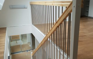 Rak-trappa vitmålade vanger i 40 mm furu, klarlackade trappsteg och rostfria räckesståndare