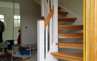 Lantlig U-trappa med lackade ektrapp steg och vita vanger och räckesståndare.