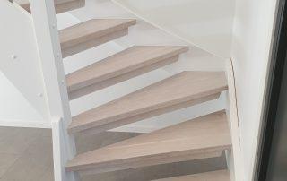 Öppen L-trappa. Steg i vitlackad ek och sidovang i vitmålat utförande. Räcke i rostfritt stål.